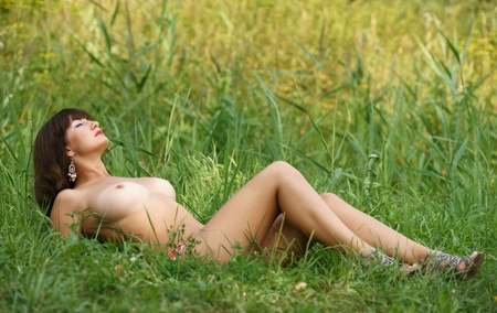 The bared girl in a grass
