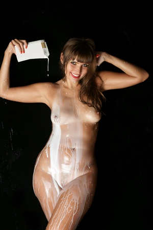 The bared girl is poured by milk