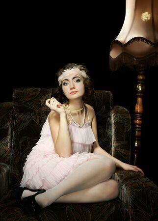 The girl in 30s style on an armchair photo