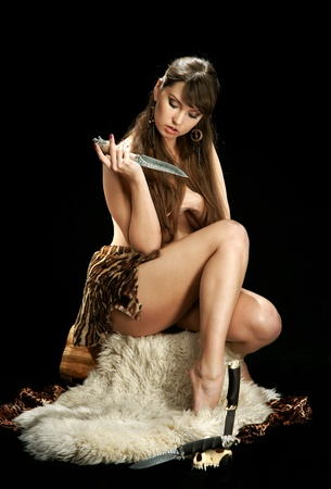 Amazon woman on a sheep skin with a knife photo