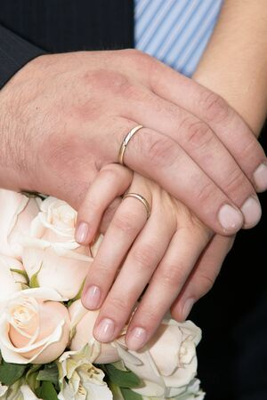 newly married - hands with gold rings on a beautifull wedding bouquet photo