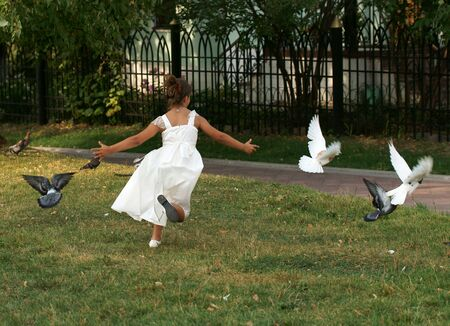 overindulgence: The girl in park drives pigeons