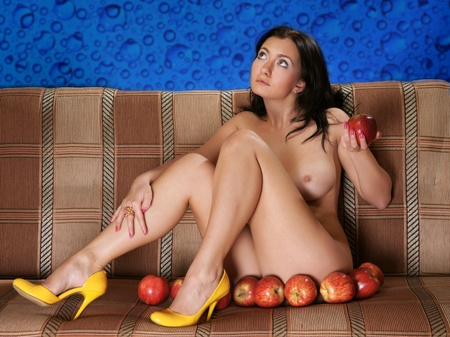 A nude girl with apples on a sofa photo