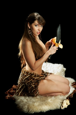 Amazon woman peels skin off an apple with a knife photo