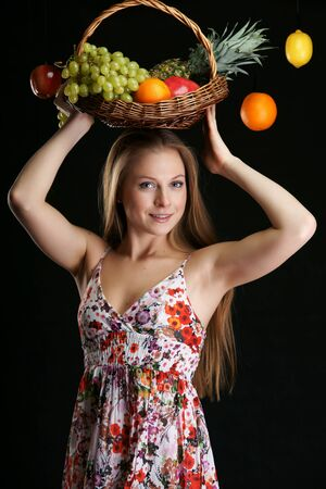 The beautiful girl with basket of fruit photo