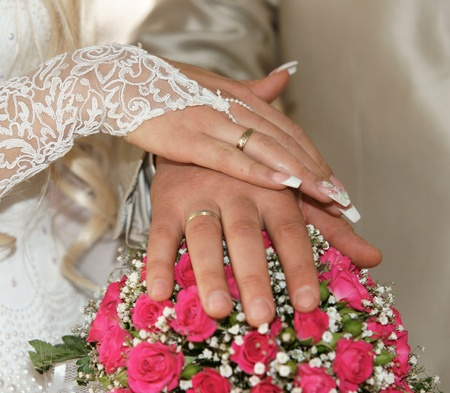 newly married - hands with gold rings on a beautifull wedding bouquet