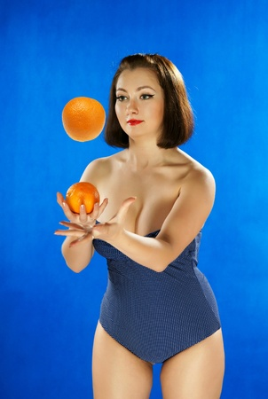 The girl in a bathing suit juggles with oranges photo