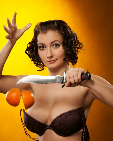 The girl with a knife and an orange Stock Photo - 13539777