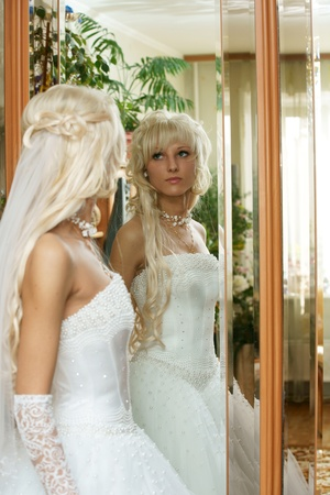 The beautiful bride looks in a mirror. photo