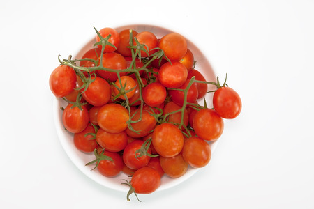 cherry tomatoes s in bowl, isolated on white background. Top view