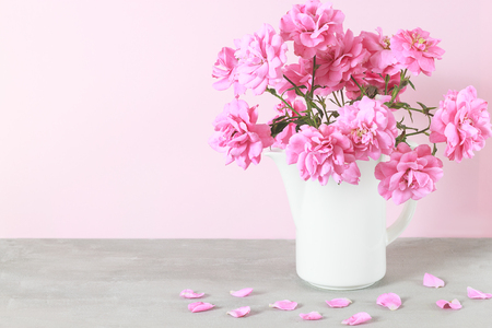 Beautiful pink rose flowers bouquet in white vase on gray table. Flower background. Copy space for message 写真素材