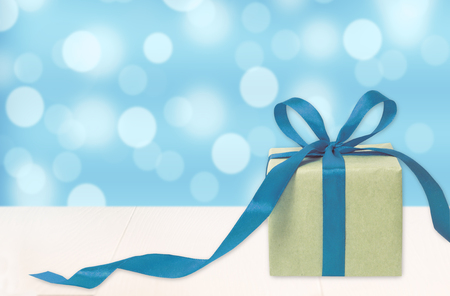 Gift box against light blue bokeh background. Holiday greeting card. Festive concept Stock Photo