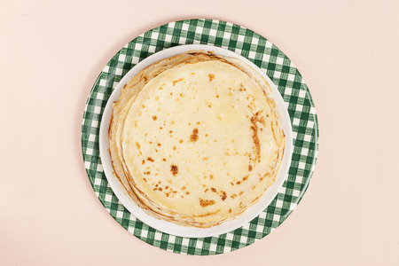 Pancakes on a saucer on a kitchen towel. Many pancakes are stacked. Thin pancakes with crispy crust. Maslenitsa. Pancakes for breakfast and carnival. Food background. Top view