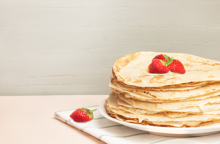 Pancakes with strawberry, traditional for Shrove Tuesday in English-style. Traditional classic thin golden flapjack on the plate and napkin