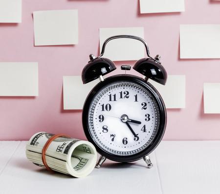 Dollars rooled and alarm clock - Concept saving  money