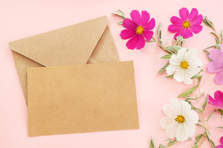 Flowers composition and envelope blank. colorful flowers on pink background. Easter, spring, summer concept. Flat lay, top view, copy space
