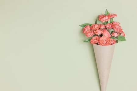 Boeket van kleine rode rozen in vintage papier op tafel. Bovenaanzicht, plat, overhead. Uitnodigingskaart. moederdag achtergrond. Uitnodigingskaart met bloemen Stockfoto