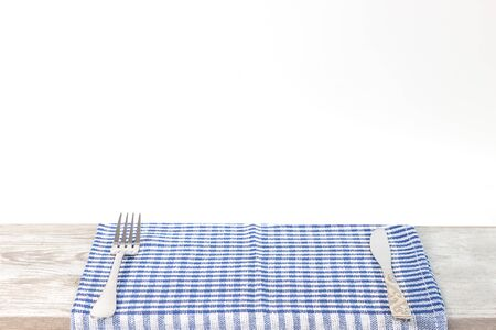 Empty wooden desk table and red checked tablecloth or napkin over gray wallpaper background