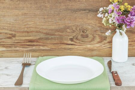 Empty plate on tablecloth or napkin on wooden table over wooden background. table setting.