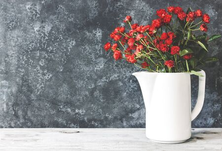 Roses in retro white vase on wood table on grunge blue wall with copy space. Beautiful bouquet of roses
