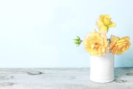 Yellow roses in retro white vase on wood table on blue wall with copy space. Beautiful bouquet of roses Stock fotó
