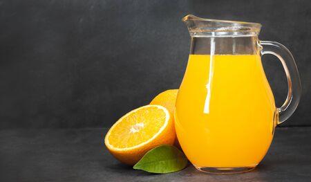 Fresh orange juice in the glass jug , fresh oranges on dark table. Fruit beverage