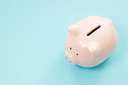 Piggy bank money on blue background. Savings concept Stock fotó