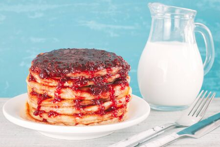 Pancakes with raspberries jam on plate on wooden table. Stack of pancakes for breakfast. Maslenitsa. Food background. Stock fotó