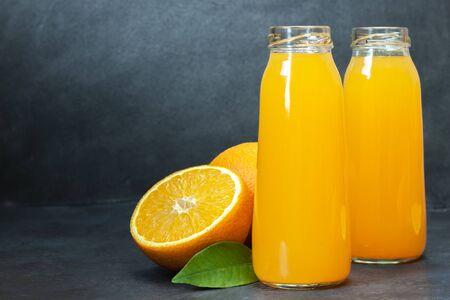 Fresh orange juice in the glass bottle, fresh oranges on dark table. Fruit beverage