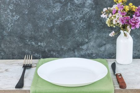 Empty plate on tablecloth or napkin on wooden table over dark background. table setting.