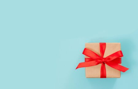 Gift box or present wrapped with red bow on blue background. Top view, flat lay