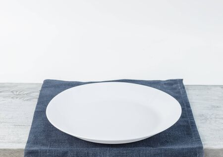Empty plate on blue tablecloth or napkin on wooden table over grunge grey background Stock Photo