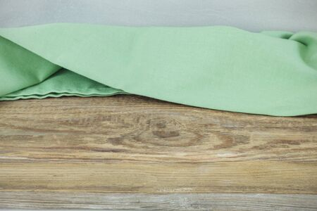 Crumpled napkin on wooden table over grey wall background, Empty space for product
