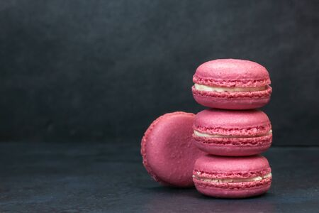Cake macaron on dark background with copy space for text. tasty french dessert is pink macaroons