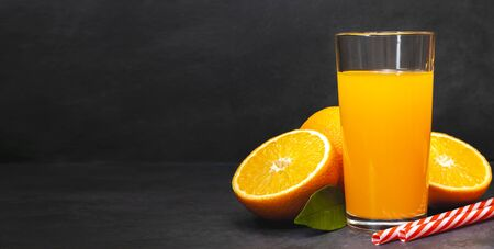 Gass of fresh orange juice with fresh fruits on dark table. Citrus beverage on desk and copy space for text. Detox