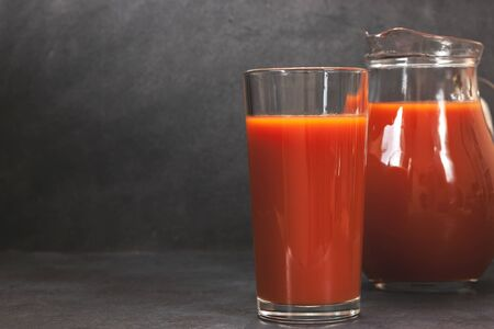 Fresh tomato juice in glass on dark table. Vegetable drink