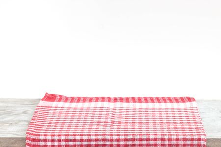 Empty wooden desk table and red checked tablecloth napkin over gray wallpaper background