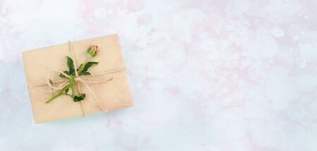 Present or gift box in craft paper with rose on pink background. Top view, flat lay, overhead. Stock Photo