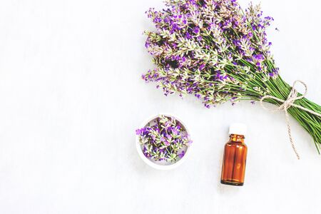 Lavender flower bouquet, bottle with oil on wood background. Purple flower on table. Top view, flat lay design