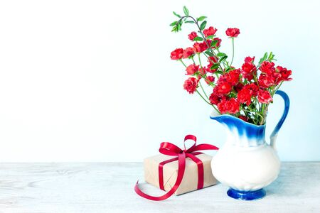 Present or gift box in a craft paper with red ribbon bow on white background. Greeting card for Valentine or Mother Day.