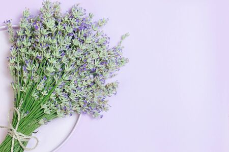 Lavender flower bouquet on lilac background. Purple flower on table. Top view, flat lay design 写真素材