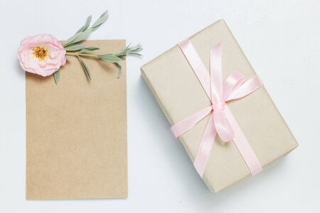 Gift box with rose on blue background. Vintage present. Gift box with pink ribbon and bow. Greeting card for Birthday, Womens or Mothers Day