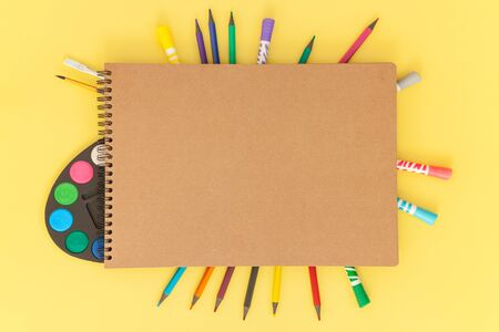 Education or back to school concept. Top view of colorful school supplies with books, color pencils, pen cutter clips on yellow background. Flat lay
