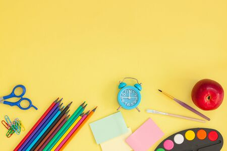 Education or back to school concept. Top view of colorful school supplies with books, color pencils, pen cutter clips and red apple on yellow background. Flat lay