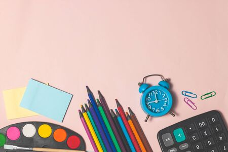 Education or back to school concept. Top view of colorful school supplies with books, color pencils, pen cutter clips on pink background. Flat lay