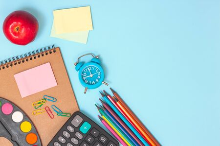 Education or back to school concept. Top view of colorful school supplies with books, color pencils, pen cutter clips and red apple on blue background. Flat lay