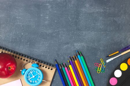 Education or back to school concept. Top view of colorful school supplies with books, color pencils, calculator, pen cutter clips and red apple on chalkboard background. Flat lay Zdjęcie Seryjne