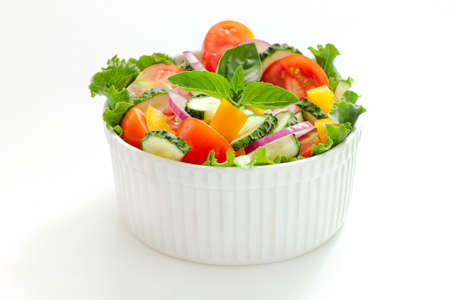 Green salad with tomato and fresh vegetables isolated on white background.