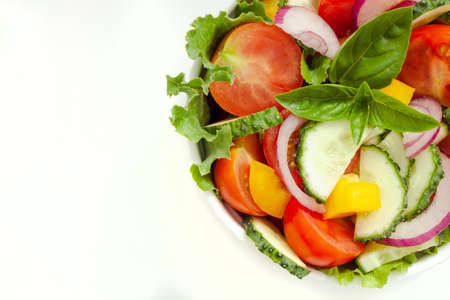 Green salad with tomato and fresh vegetables isolated on white background. Top view