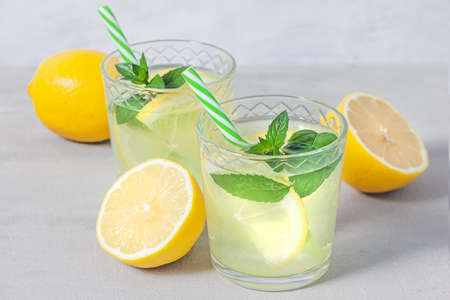 Lemon lemonade with herb on gray background. Summer drink. Traditional lemonade with lemon mint and ice on gray concrete table